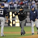 Second base umpire Adrian Johnson, center, calls for an instant replay after talking to Milwaukee Brewers manager Ron Roenicke, right, and Matt Garza during the first inning of a baseball game against the Philadelphia Phillies, Wednesday, April 9, 2014, i