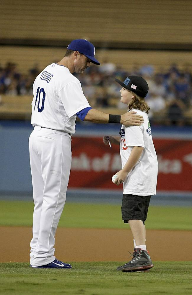 Ian Crain, right, a 10-year-old son of Riverside police officer Michael Crain, who was shot and killed by Christopher Dorner, talks to Los Angeles Dodgers' Michael Young on the field before a baseball game against the Arizona Diamondbacks on Wednesday, Sept. 11, 2013, in Los Angeles