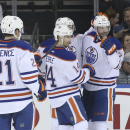 Edmonton Oilers left wing Benoit Pouliot (67) celebrates with defenseman Justin Schultz (19), right wing Jordan Eberle (14) and defenseman Andrew Ference (21) after scoring during the second period of an NHL hockey game against the New York Rangers at Mad