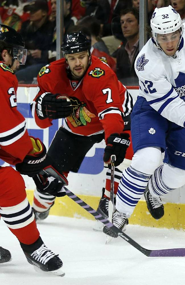 Chicago Blackhawks defensemen Duncan Keith (2) and Brent Seabrook (7) battle vie the puck with Toronto Maple Leafs left wing Josh Leivo (32) during the first period of an NHL hockey game Saturday, Oct. 19, 2013, in Chicago
