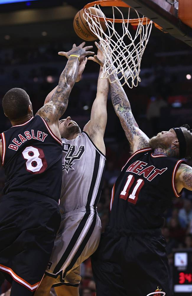 Miami Heat players Michael Beasley (8) and Chris Andersen (11) block San Antonio Spurs' Manu Ginbobil (20) during the first half of a NBA basketball game in Miami, Sunday, Jan. 26, 2014