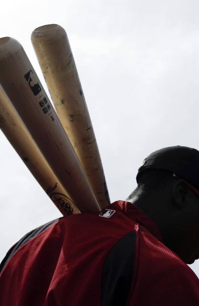 Arizona Diamondbacks shortstop Didi Gregorius carries three bats on his shoulder as he stops to sign autographs with fans before playing the Kansas City Royals in an exhibition spring training baseball game Wednesday, March 5, 2014, in Scottsdale, Ariz