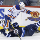 Edmonton Oilers' Ryan Nugent-Hopkins (93) trips over Winnipeg Jets' Jacob Trouba (8) during the third period of an NHL hockey game in Winnipeg, Manitoba on Wednesday, Dec. 3, 2014 The Associated Press
