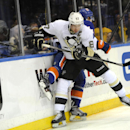 Pittsburgh Penguins center Sidney Crosby (87) slams New York Islanders' Calvin de Haan (44) against the boards in the third period of an NHL hockey game on Tuesday, Dec. 3, 2013, in Uniondale, N.Y. Crosby scored two goals during the Penguins 3-2 win in ov