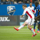 New England Revolution's Kelyn Rowe (11) breaks away from Montreal Impact's Hassoun Camara to score a goal during the first half of an MLS soccer game in Montreal, Saturday, Oct. 11, 2014 The Associated Press