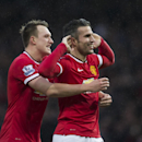 Manchester United's Robin van Persie, right, celebrates with teammate Phil Jones after scoring during the English Premier League soccer match between Manchester United and Liverpool at Old Trafford Stadium, Manchester, England, Sunday Dec. 14, 2014