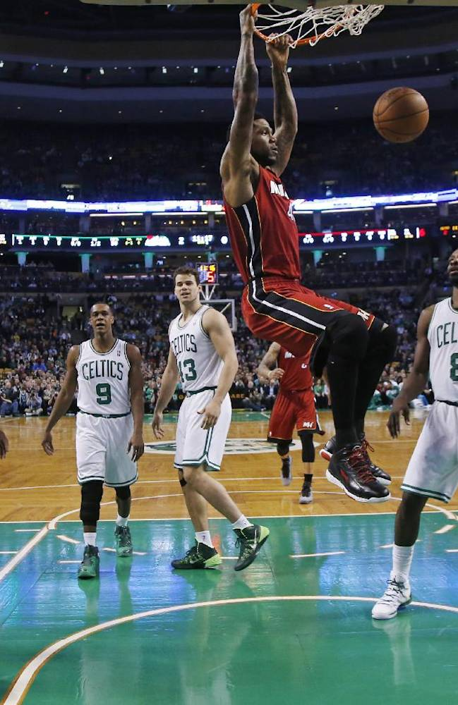 Miami Heat forward Udonis Haslem (40) dunks as Boston Celtics forward Brandon Bass (30), guard Rajon Rondo (9), center Kris Humphries (43) and forward Jeff Green (8) watch in the first quarter of an NBA basketball game in Boston Wednesday, March 19, 2014