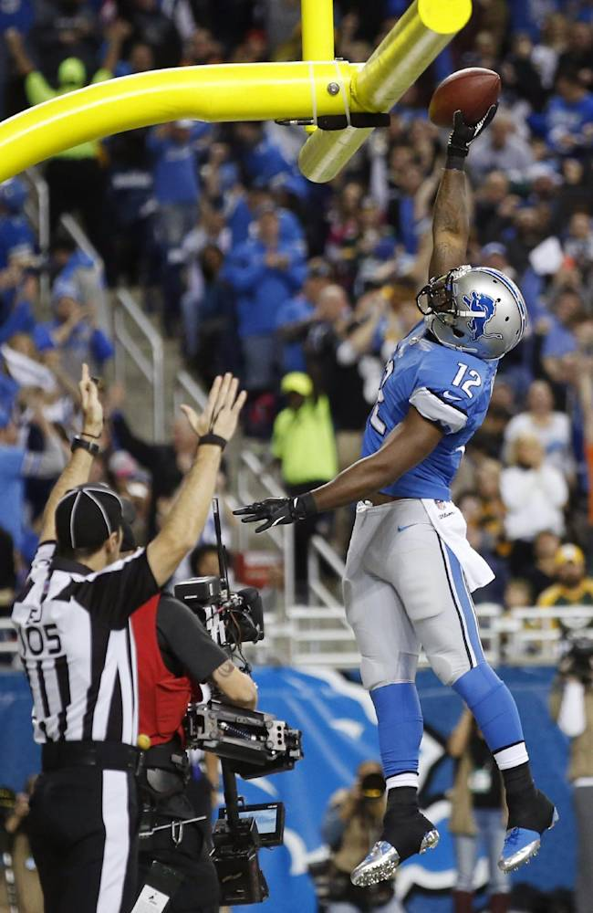 Detroit Lions wide receiver Jeremy Ross (12) dunks the ball after scoring on a 5-yard pass reception during the second quarter of an NFL football game against the Green Bay Packers at Ford Field in Detroit, Thursday, Nov. 28, 2013