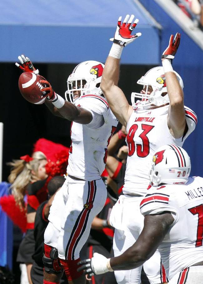 Louisville's Senorise Perry, left and Ryan Hubbell celebrate Perry's third quarter touchdown in an NCAA college football game against Kentucky on Saturday, Sept. 14, 2013, in Lexington, Ky. Louisville won 27-13