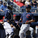 Cleveland Indians' Nick Swisher (33) scores on a hit by Carlos Santana during the first inning of an exhibition spring training baseball game Saturday, March 8, 2014, in Peoria, Ariz. San Diego Padres' Rene Rivera watches as Swisher scores The Associated