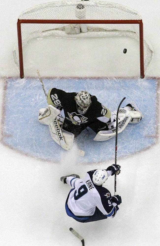 Winnipeg Jets' Evander Kane (9) backhands a shot past Pittsburgh Penguins goalie Marc-Andre Fleury (29) for his first of two goals in the second period of an NHL hockey game in Pittsburgh, Sunday, Jan. 5, 2014. The Penguins won 6-5