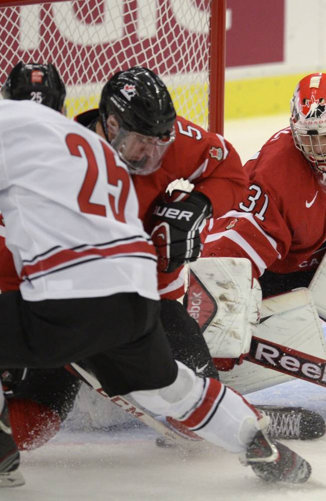Canadian goalie Zachary Fucale makes a save against Switzerland during first period action in a quarterfinal match at the world junior hockey tournament in Malmo, Sweden, Thursday, Jan 2, 2014. At left is Switzerland's Dario Simion (25) and at center is Canada's Aaron Ekblad (5). AP Photo/The Canadian Press, Frank Gunn)