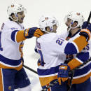 New York Islanders' Kyle Okposo (21) celebrates his game-winning goal with teammates Cal Clutterbuck, right, and John Tavares during the shootout of an NHL hockey game on Tuesday, Dec. 10, 2013, in San Jose, Calif. New York won 3-2. (AP Photo/Marcio Jose Sanchez)