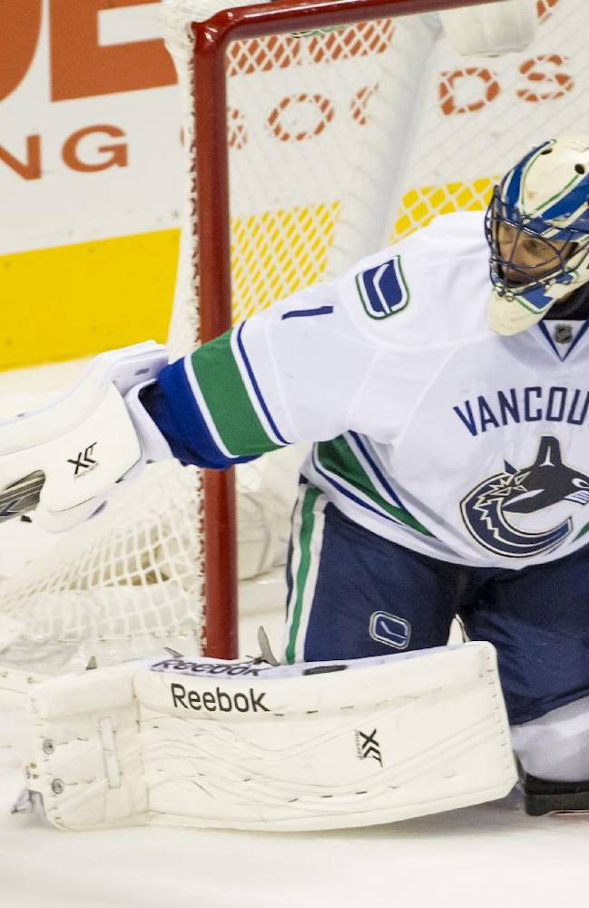 Vancouver Canucks' Roberto Luongo swats away the puck during the third period of an NHL hockey game against the Philadelphia Flyers, Tuesday, Oct. 15, 2013, in Philadelphia. The Canucks won 3-2