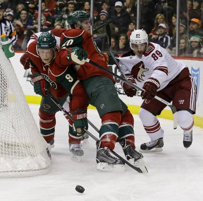 Minnesota Wild defenseman Ryan Suter (20) gets caught between Wild center Mikko Koivu (9), of Finland, and Phoenix Coyotes left wing Mikkel Boedker (89), of Denmark, as they chase the puck during the second period of an NHL hockey game in St. Paul, Minn., Wednesday, Nov. 27, 2013