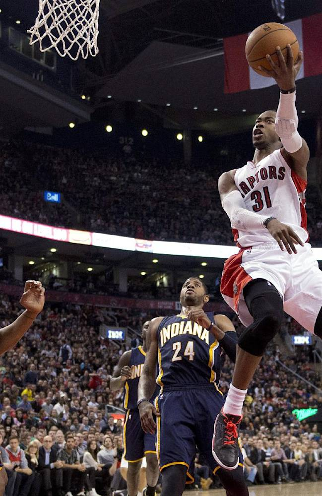 Toronto Raptors guard Terrence Ross (31) soars past Indiana Pacers forwards David West, left, and Paul George (24) during the first half of an NBA basketball game Friday, April 4, 2014, in Toronto