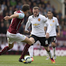 Manchester United's Wayne Rooney, center, keeps the ball from Burnley's Michael Duff during their English Premier League soccer match at Turf Moor Stadium, Burnley, England, Saturday Aug. 30, 2014