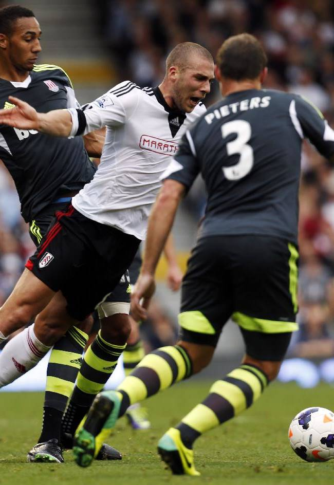 Fulham's Pajtim Kasami, center, is fouled by Stoke City's Steven Nzonzi, left, during an English Premier League soccer match at the Craven Cottage ground in London, Saturday, Oct. 5, 2013. Fulham won the match 1-0