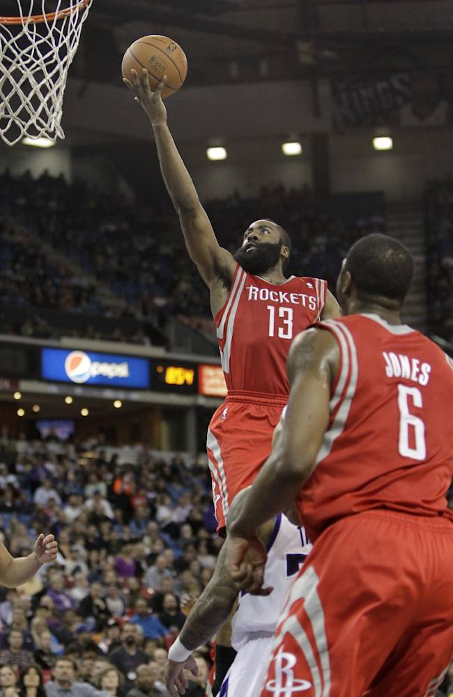 Houston Rockets guard James Harden, left, drives to the basket during the third quarter of an NBA basketball game agains the Sacramento Kings in Sacramento, Calif., Tuesday Feb. 25, 2014.  Harden scored 43 points in the Rockets 129-103 victory