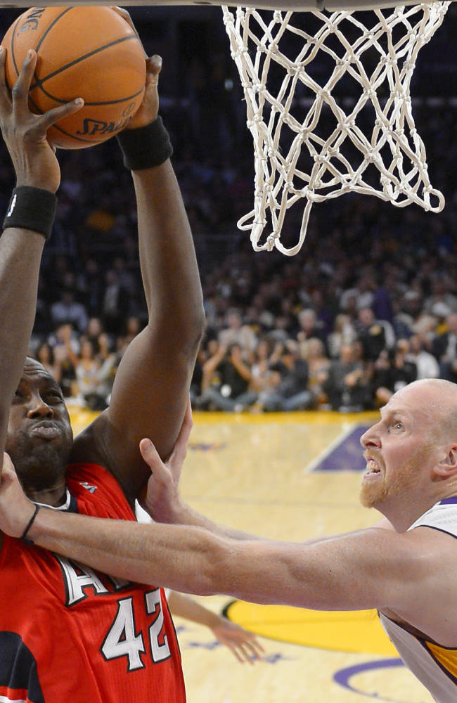 Atlanta Hawks forward Elton Brand, left, is fouled by Los Angeles Lakers center Chris Kaman as he puts up a shot during the first half of their NBA basketball game, Sunday, Nov. 3, 2013, in Los Angeles