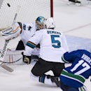 San Jose Sharks goalie Alex Stalock, left, stops a shot from Vancouver Canucks right wing Radim Vrbata (17) as Sharks Jason Demers looks on during the first period of an NHL preseason hockey game in Vancouver, British Columbia, Tuesday, Sept. 23, 2014. Th