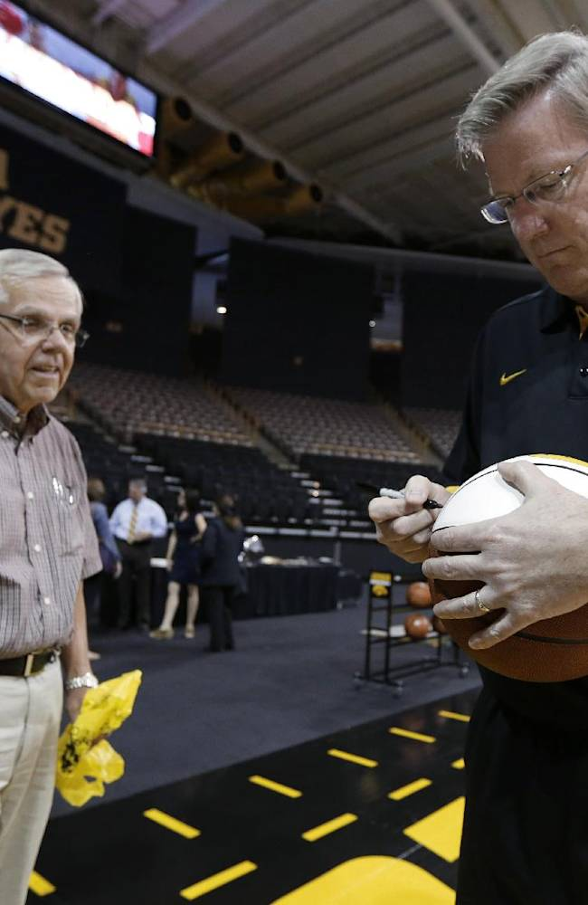 Iowa coach Fran McCaffery autographs a basketball for Iowa fan George Karr, left, during the NCAA college basketball team's media day, Wednesday, Oct. 9, 2013, in Iowa City, Iowa.  McCaffery is in his fourth year as Iowa's coach