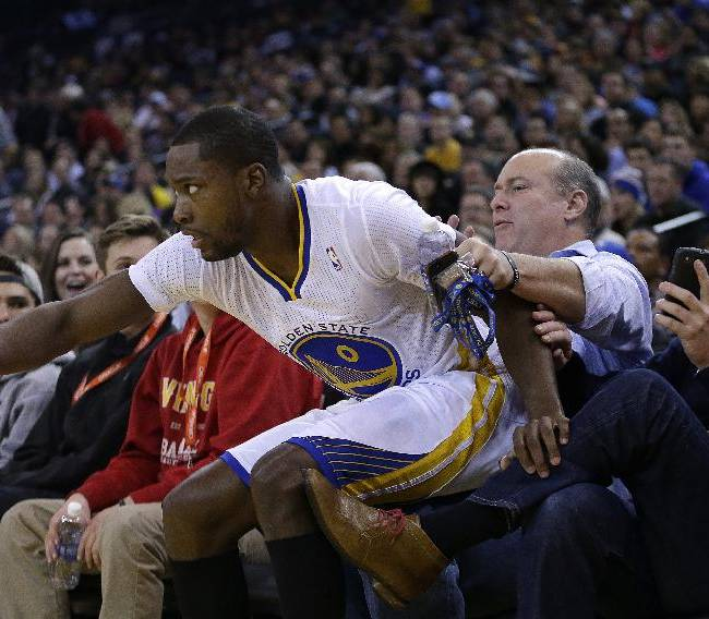 Golden State Warriors' Toney Douglas lands on fans during the second half of an NBA basketball game against the Los Angeles Lakers, Saturday, Dec. 21, 2013, in Oakland, Calif