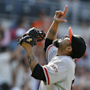 San Francisco Giants closer Sergio Romo points to the heavens after escaping a ninth inning jam and saving the Giants 4-3 victory over the San Diego Padres in a baseball game Sunday, April 20, 2014, in San Diego. The Giants savaged the last game of the t