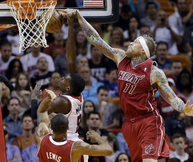 Atlanta Hawks' Shelvin Mack, left, shoots as Miami Heat's Chris Andersen (11) deflects the ball in the first half of an NBA basketball game, Monday, Dec. 23, 2013, in Miami