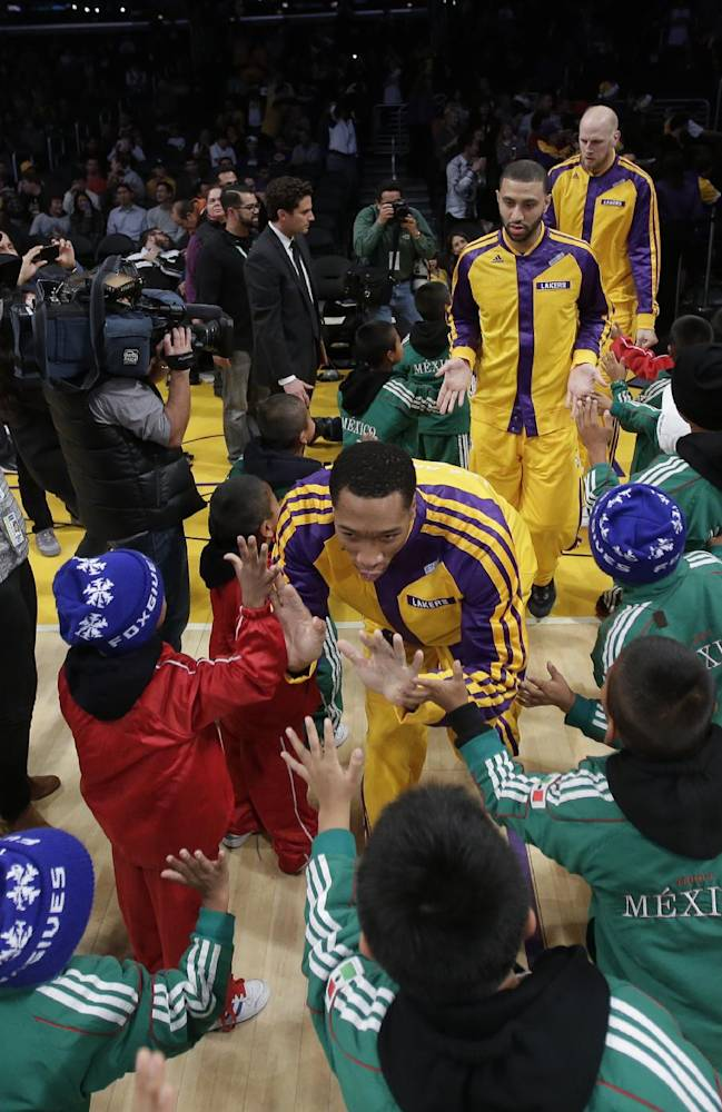 Members of Triqui kids basketball team, made up of children from the mountainous  mountainous region of Oaxaca, Mexico, greet the Los Angeles Lakers before an NBA basketball game against the Minnesota Timberwolves in Los Angeles, Friday, Dec. 20, 2013