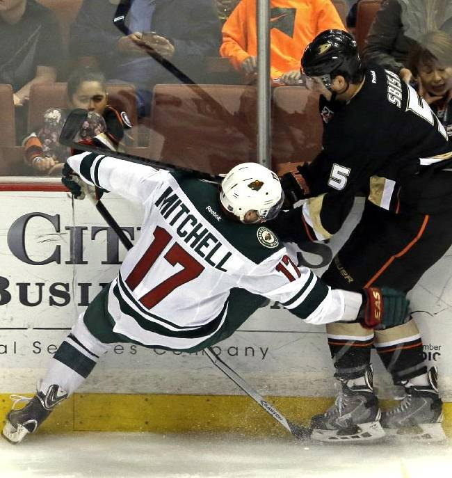 Anaheim Ducks defenseman Luca Sbisa (5), of Italy, and Minnesota Wild center Torrey Mitchell (17) tangle in the first period of an NHL hockey game in Anaheim, Calif., Tuesday, Jan. 28, 2014