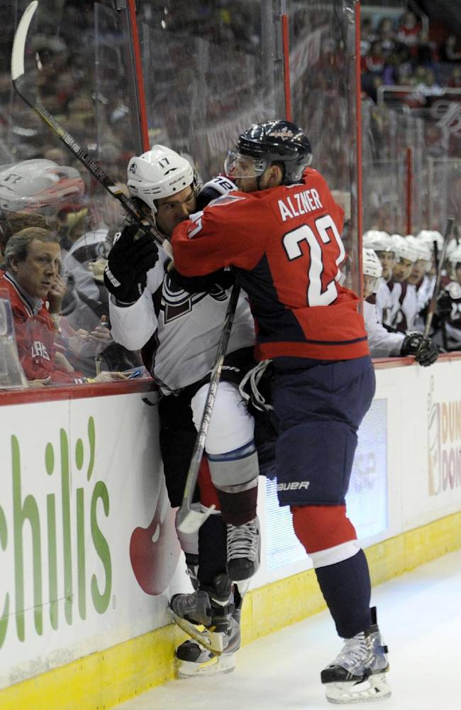 Washington Capitals defenseman Karl Alzner (27) checks Colorado Avalanche right wing Steve Downie (17) into the boards during the second period an NHL hockey game, Saturday, Oct. 12, 2013, in Washington