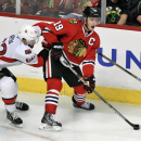 Chicago Blackhawks' Jonathan Toews (19) looks to pass against Ottawa Senators' Eric Gryba (62) during the third period of an NHL hockey game in Chicago, Sunday, Oct. 26, 2014. Chicago won 2-1 The Associated Press