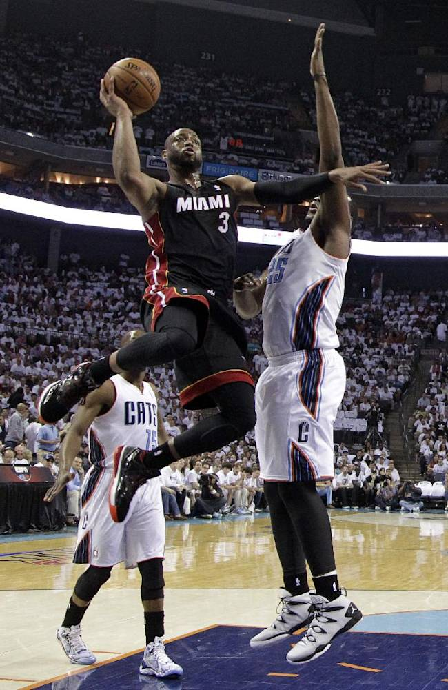 Miami Heat's Dwyane Wade (3) drives past Charlotte Bobcats' Al Jefferson (25) and Kemba Walker (15) during the first half in Game 3 of an opening-round NBA basketball playoff series in Charlotte, N.C., Saturday, April 26, 2014