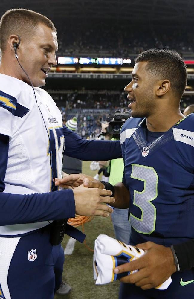 Seattle Seahawks quarterback Russell Wilson (3) visits with San Diego Chargers quarterback Philip Rivers after the Seahawks defeated the Chargers 41-14 in a preseason NFL football game, Friday, Aug. 15, 2014, in Seattle