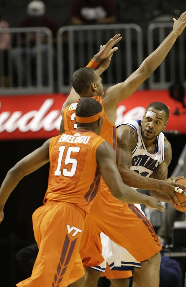 Seton Hall's Gene Teague, right, looks to pass away from Virginia Tech's Trevor Thompson and Ben Emelogu (15) during the first half of a consolation game in the Coaches vs. Cancer NCAA college basketball game on Saturday, Nov. 23, 2013, in New York