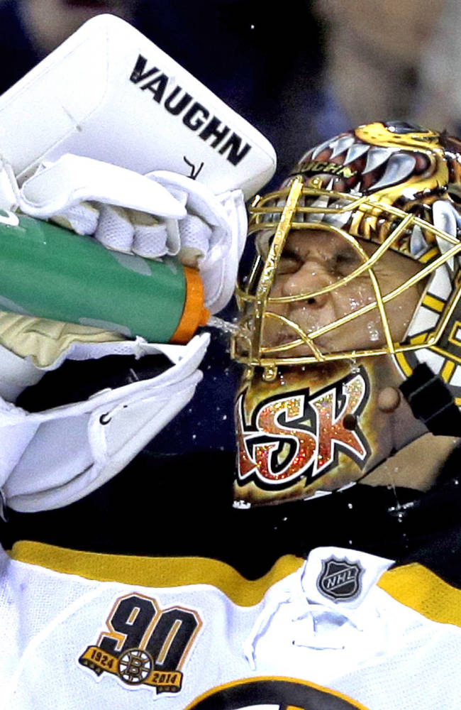 Boston Bruins goalie Tuukka Rask, of Finland, sprays his face after giving up a goal to St. Louis Blues' Jaden Schwartz during the second period of an NHL hockey game Thursday, Feb. 6, 2014, in St. Louis