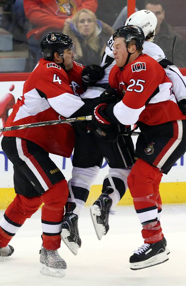 Ottawa Senators' Chris Phillips (4) and teammate Chris Neil (25) collide with Los Angeles King' Daniel Carcillo (17) during the seond period of an NHL hockey game in Ottawa, Saturday, Dec. 14, 2013