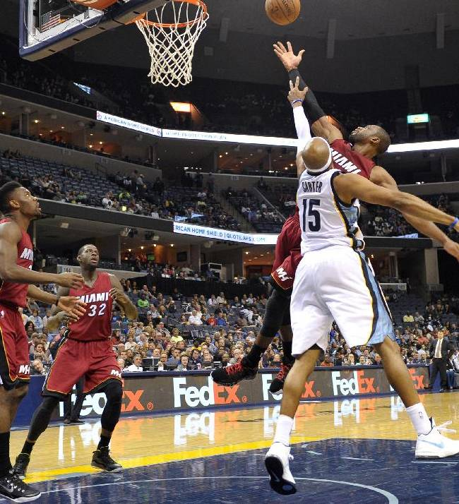 Miami Heat guard Dwyane Wade shoots over Memphis Grizzlies guard Vince Carter (15) in the first half of a preseason NBA basketball game Friday, Oct. 24, 2014, in Memphis, Tenn
