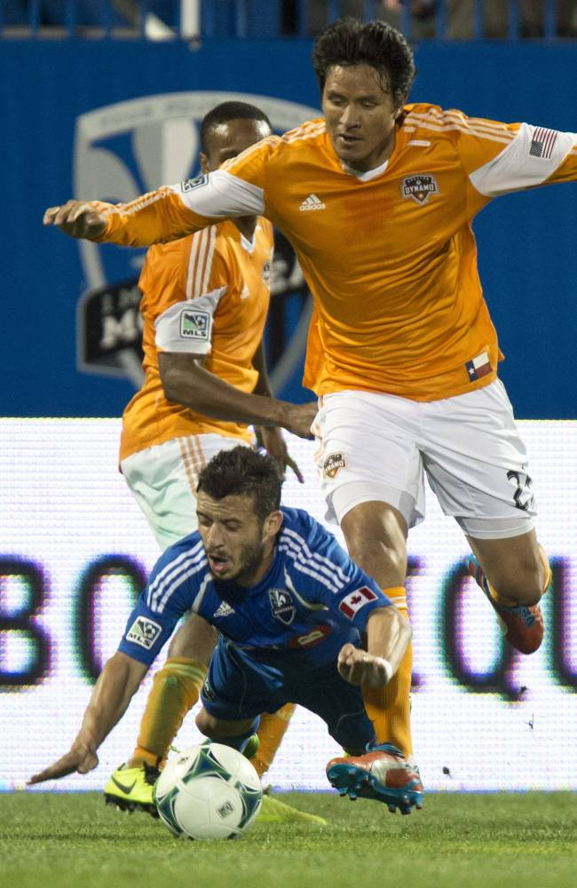 Montreal Impact's Felipe Martins is knocked down by Houston Dynamo's Brian Ching during second-half MLS soccer game action on Wednesday, June 19, 2013, in Montreal. The Impact won 2-0