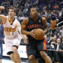 Toronto Raptors' Kyle Lowry, right, drives to the basket past the defense of Phoenix Suns' Goran Dragic (1), of Slovenia, during the first half of an NBA basketball game onFriday, Dec. 6, 2013, in Phoenix The Associated Press