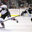 Colorado Avalanche's Tyson Barrie, left, passes the puck against Los Angeles Kings' Dwight King during the first period of an NHL hockey game on Saturday, Nov. 23, 2013, in Los Angeles The Associated Press