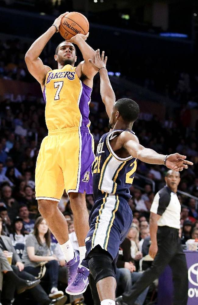 Los Angeles Lakers guard Xavier Henry, left, shoots over the top of Utah Jazz guard Ian Clark during the second half of a preseason NBA basketball game in Los Angeles, Tuesday, Oct. 22, 2013