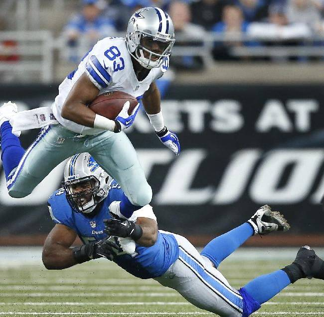 Dallas Cowboys wide receiver Terrance Williams (83) jumps to elude Detroit Lions outside linebacker DeAndre Levy (54) in the second half of an NFL football game in Detroit, Sunday, Oct. 27, 2013