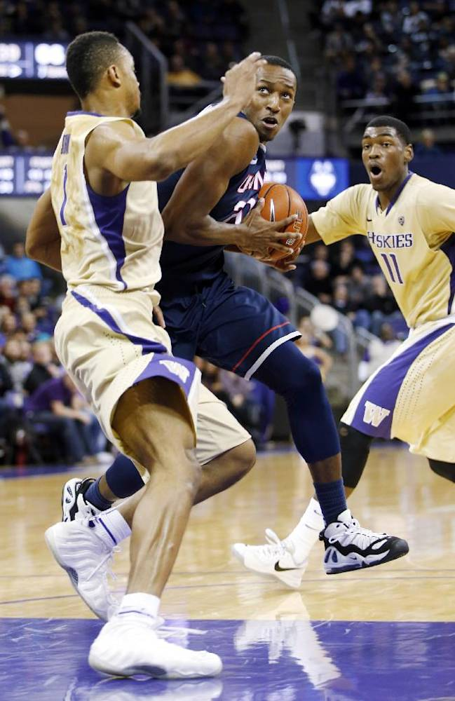Connecticut's Lasan Kromah, center, drives between Washington's Darin Johnson, left, and Mike Anderson, right, to the basket in the second half of an NCAA college basketball game in Seattle on Sunday, Dec. 22, 2013. UConn won 82-70