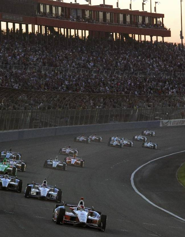 AJ Allmendinger, right, leads a pack of cars around turn one during the IndyCar auto race at the Auto Club Speedway, Saturday, Oct. 19, 2013, in Fontana, Calif