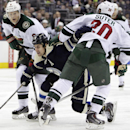 Columbus Blue Jackets' Brandon Dubinsky, center, tries to carry the puck between Minnesota Wild's Mikko Koivu, left, of Finland, and Ryan Suter during the second period of an NHL hockey game on Friday, Dec. 6, 2013, in Columbus, Ohio The Associated Press