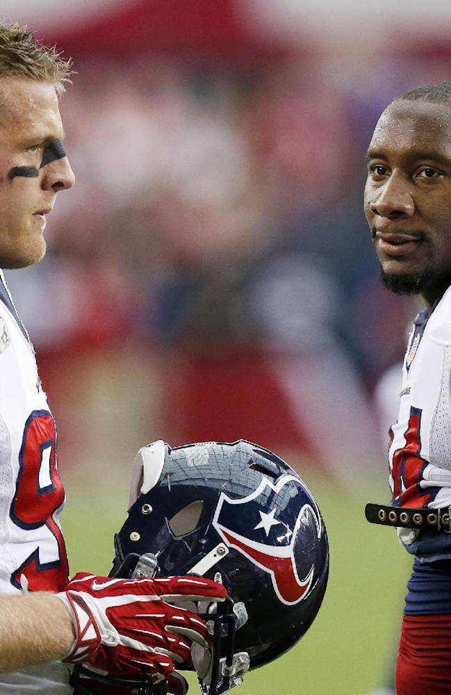 Houston Texans' J.J. Watt (99) and Antonio Smith (94) stand together as they warm up with their teammates prior to an NFL football game against the Arizona Cardinals on Sunday, Nov. 10, 2013, in Glendale, Ariz