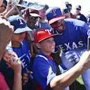 Seattle Seahawks quarterback Russell Wilson, right, gets involved with fans as he poses for a selfie before the Rangers' spring training baseball game against the San Diego Padres Saturday, March 28, 2015, in Surprise, Ariz. (AP Photo/Lenny Ignelzi)