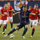 Paris Saint-Germain forward Zlatan Ibrahimovic, left, keeps the ball away from Manchester United forward Wayne Rooney, right, in the first half of an International Champions Cup soccer match, Wednesday, July 29, 2015, in Chicago. (AP Photo/Kamil Krzaczynski)